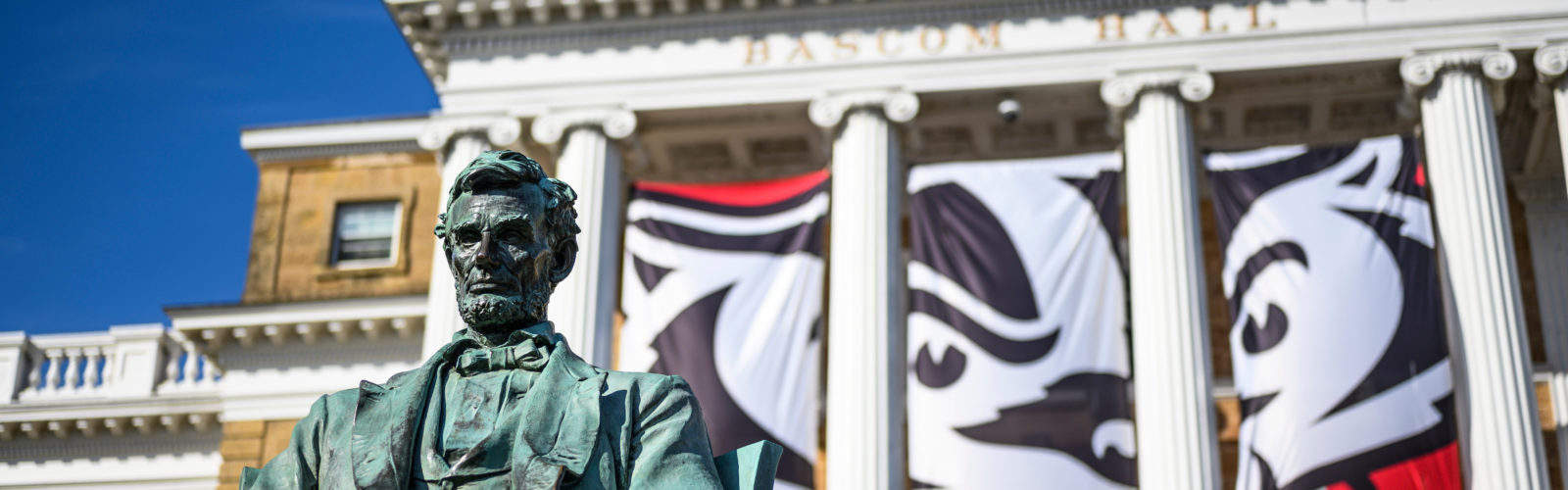 The Abraham Lincoln statue is picture in front of Bascom Hall at the University of Wisconsin-Madison on Oct. 18, 2019. Hanging in between the building's columns are banners depicting a graphic of UW-Madison mascot Bucky Badger